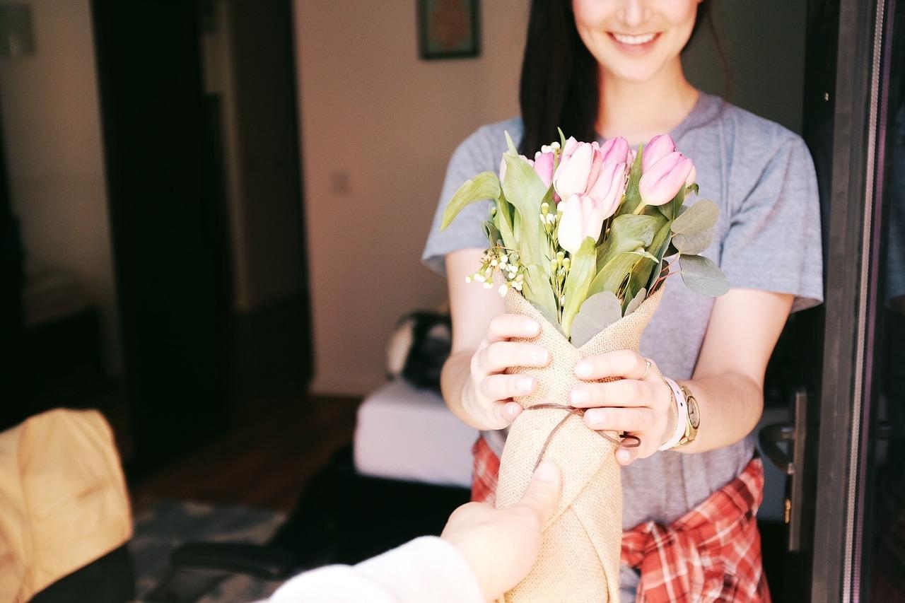 Mujer recibiendo un ramo de flores