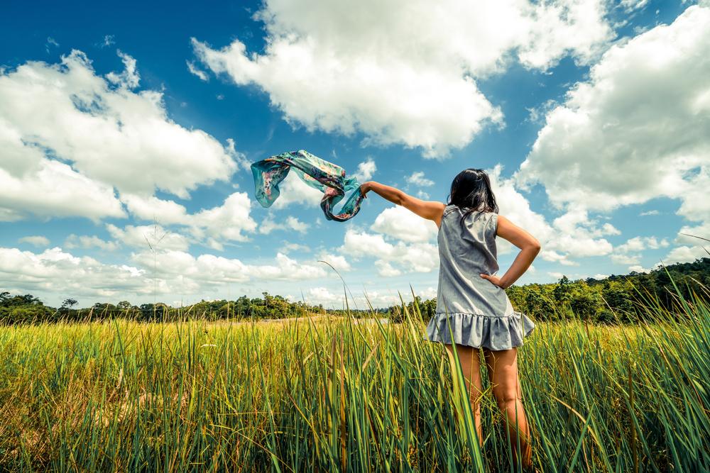 Mujer luchadora y de actitud positiva en un prado con los brazos levantados